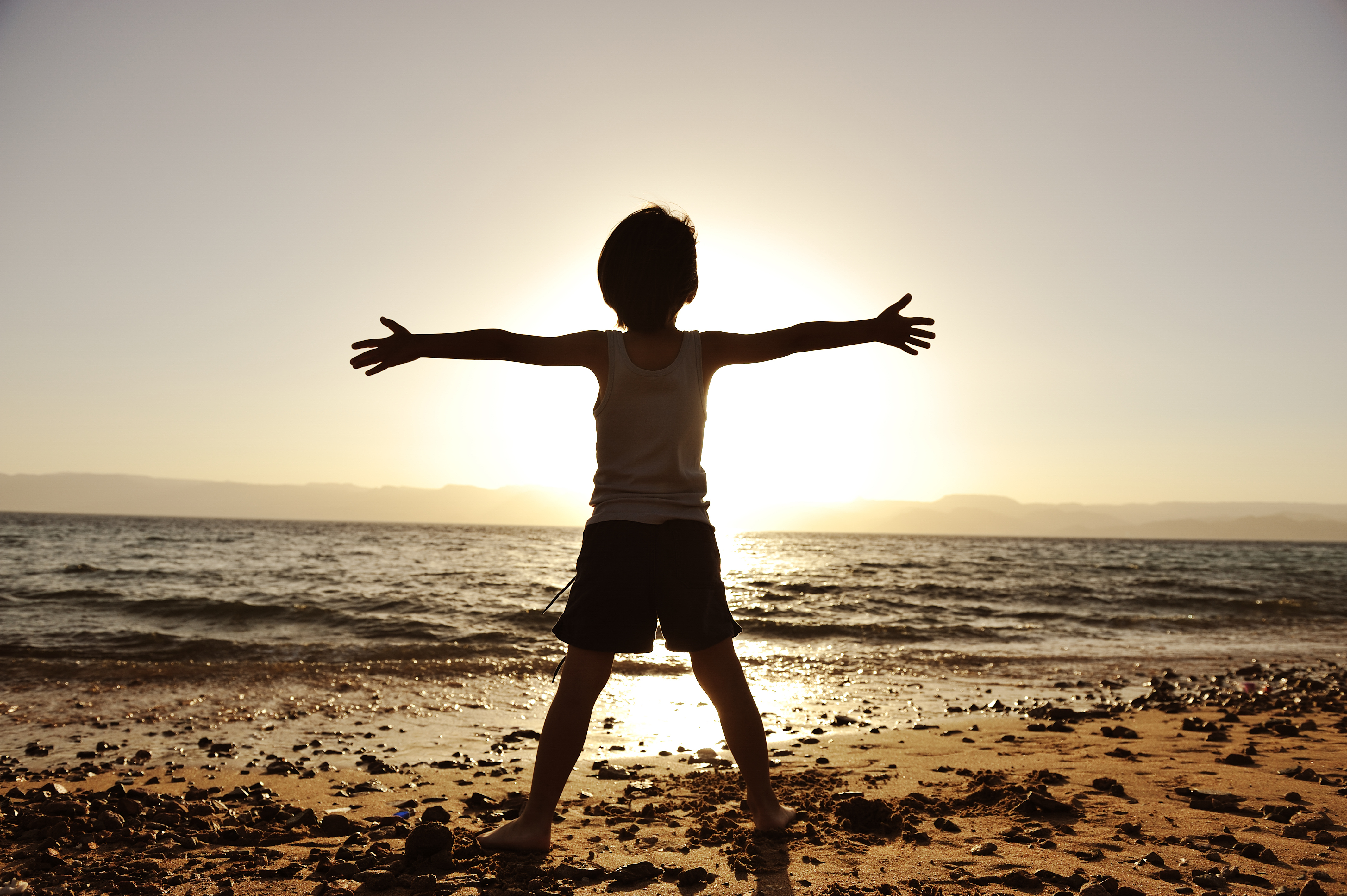 Silhouette of child on the beach, holding his hands up, hugging the su